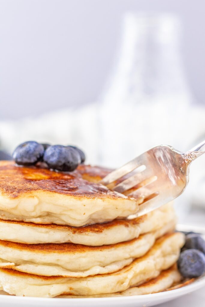 gluten free pancakes with blueberries on top and fork slicing into the stack of pancakes.