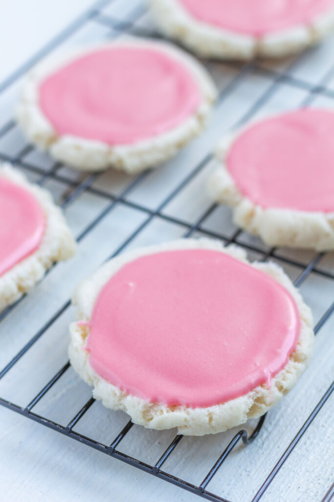 Round sugar cookies with pink frosting on a cooling rack.
