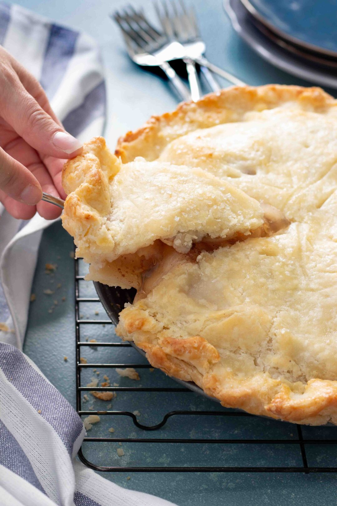 someone serving a slice of gluten free apple pie