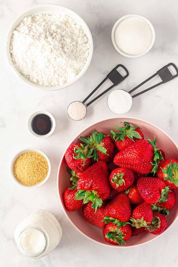 ingredients for gluten free strawberry shortcake: strawerries, sugar, floour, salt, baking powder, vanilla, and cream