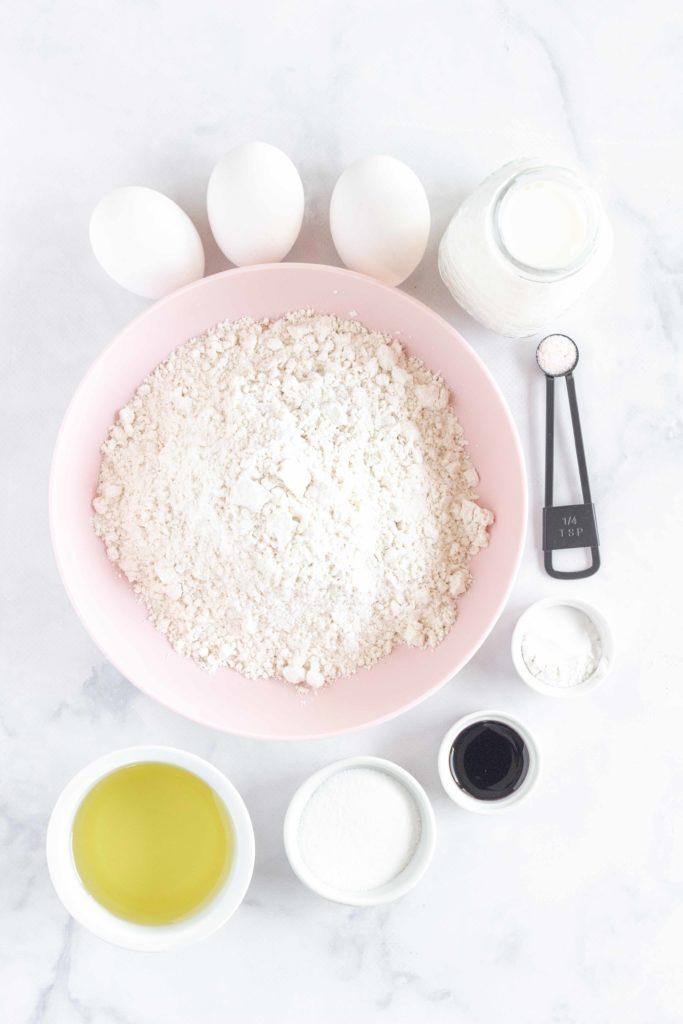 ingredients in bowls: 3 eggs, salt, baking powder/soda, vanilla, sugar, oil, milk, and a large pink bowl of flour