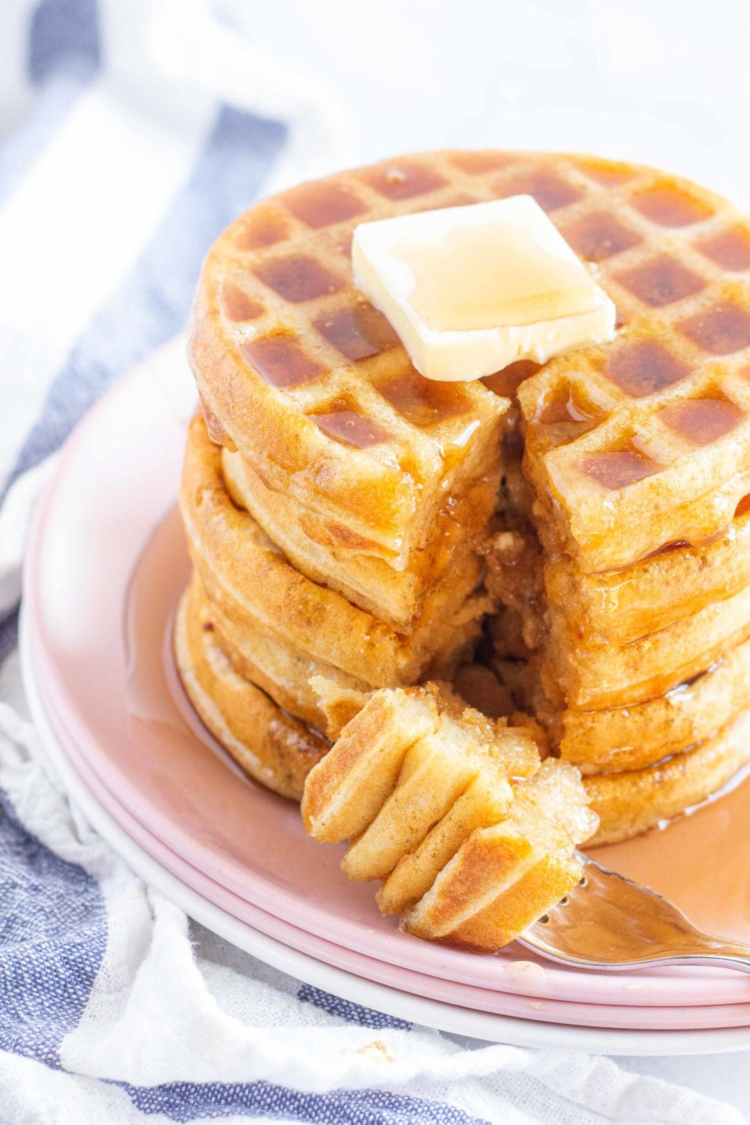 stack of gluten free waffles on a pink plate. Topped with a pat of butter and drizzled with maple syrup. A bite on a fork is sitting on the plate.